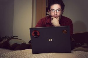IT geek sitting on a bed starring into the laptop screen